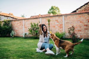 happy woman out in yard with dog